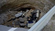Автомобиль в яме, образовавшейся в результате обвала грунта на участке автодороги, соединяющей Евпаторийское и Николаевское шоссе у Симферополя