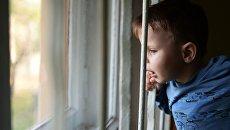 Маленький ребенок у окна. Архивное фото