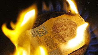 Одногривенная купюра горит на газовой конфорке.