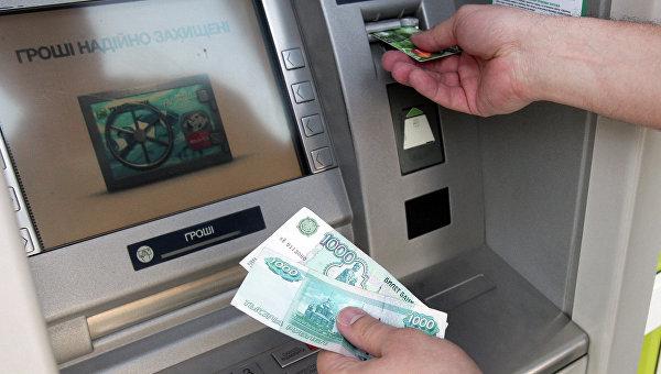 Житель Симферополя снимает наличные деньги через банкомат. Архивное фото