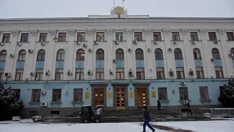 Машина убирает снег на входе в здание Совета министров Крыма