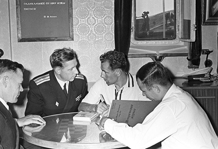 Летчики-космонавты СССР Герман Титов и Юрий Гагарин делают записи в историческом журнале моряков Черноморского флота