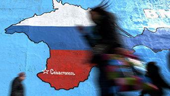 Прохожие у нарисованной на стене карты Крыма