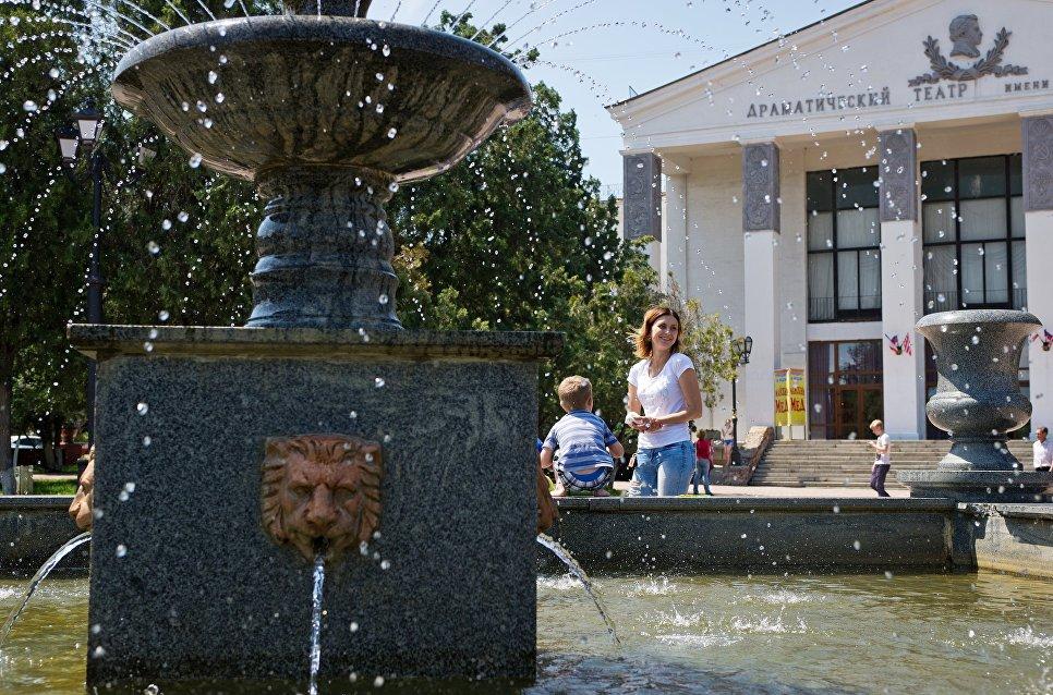 Отдыхающие у фонтана перед зданием драматического театра имени Пушкина в Керчи