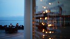 Посетители кафе отдыхают на набережной Ялты