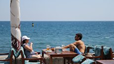 Отдыхающие в кафе на пляже в Ялте