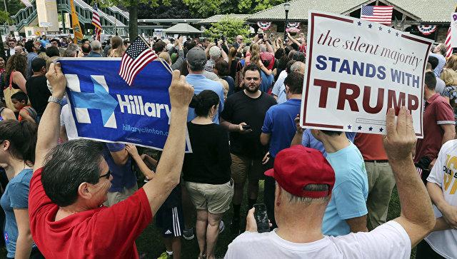 Избиратели с плакатами в поддержку кандидатов в президенты США Хилари Клинтон и Дональда Трампа