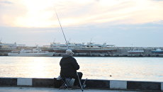 Рыбак на набережной Ялты. Архивное фото