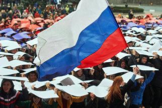 Молодые люди развернули живой флаг РФ во время флешмоба Горжусь Россией!, посвященного третьей годовщине воссоединения Крыма с Россией. Архивное фото