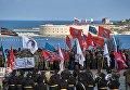 Участники митинга в честь третьей годовщины воссоединения Крыма с Россией на мысе Хрустальный в Севастополе. На дальнем плане - Севастопольская крепость