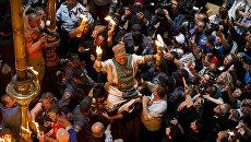 Паломники на церемонии схождения Благодатного огня в церкви Гроба Господня в Иерусалиме
