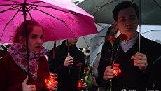 Молодые люди с цветами и свечами в память о погибших в результате взрыва в метро Санкт-Петербурга