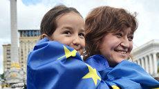 Люди с флагами ЕС И Украины на площади Независимости в Киеве. Архивное фото