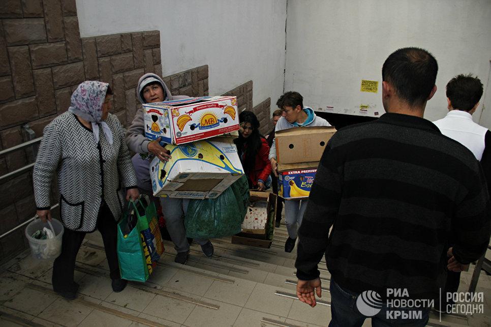 Стихийщики пытаются унести свой товар во время рейда по несанкционированной торговле в Симферополе