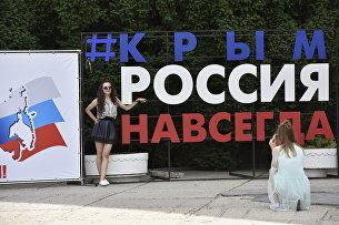 Девушки делают фото на фоне хештега #КрымРоссияНавсегда