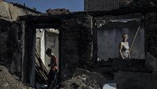 Жители в пострадавшем во время обстрела поселке Старомихайловка Донецкой области