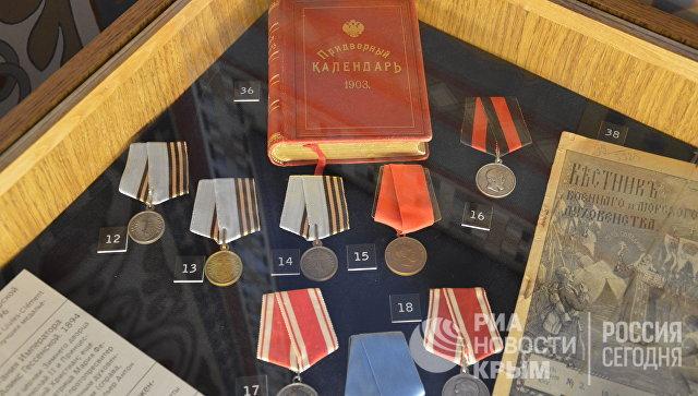 Золотые и серебряные нагрудные медали, придворный календарь императора. Экспонаты древлехранилища памяти семьи императора Николая II в Крестовоздвиженской дворцовой церкви в Ливадии