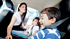 Мама пристегивает детей ремнями безопасности