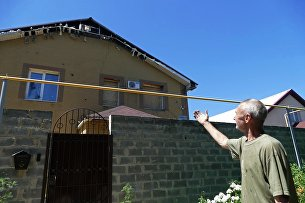 Мужчина у здания, поврежденного в результате обстрела в Донецке. 18 июля 2017