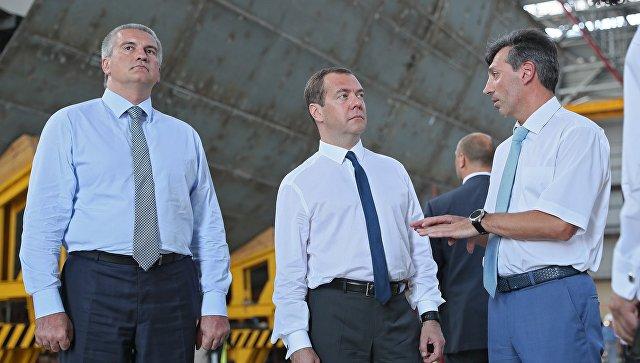 Председатель Правительства РФ Дмитрий Медведев (в центре) и глава Республики Крым Сергей Аксенов (слева) на судостроительном заводе Море в Феодосии