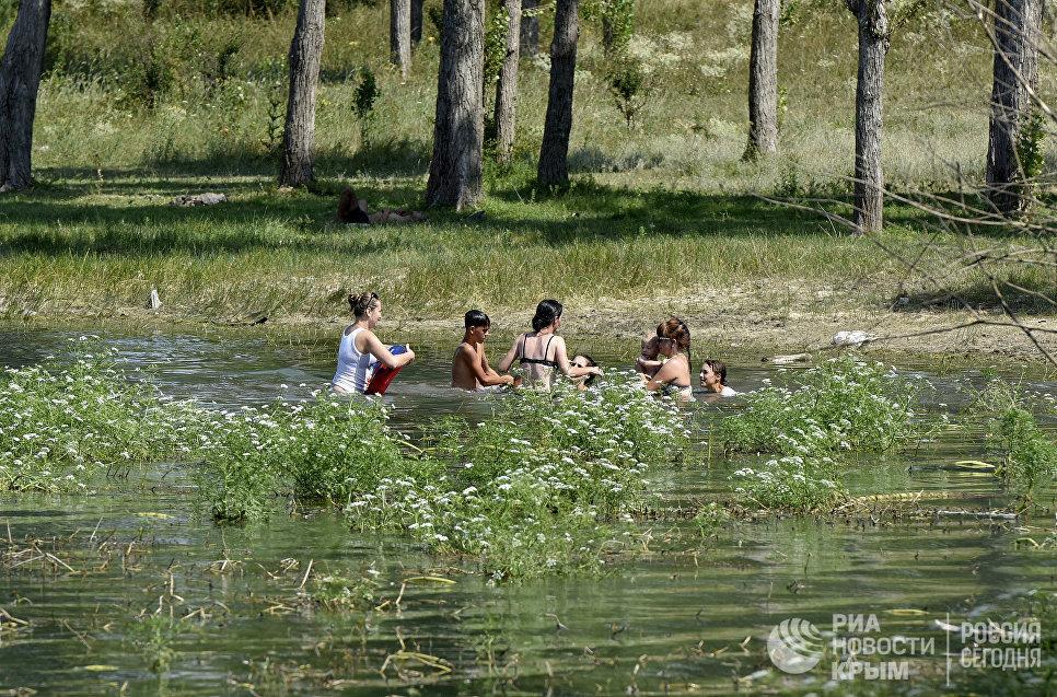 Люди купаются в Симферопольском водохранилище во время дневного зноя