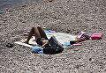 Мужчина на пляже Гурзуфа прячется от дневного зноя под вещами