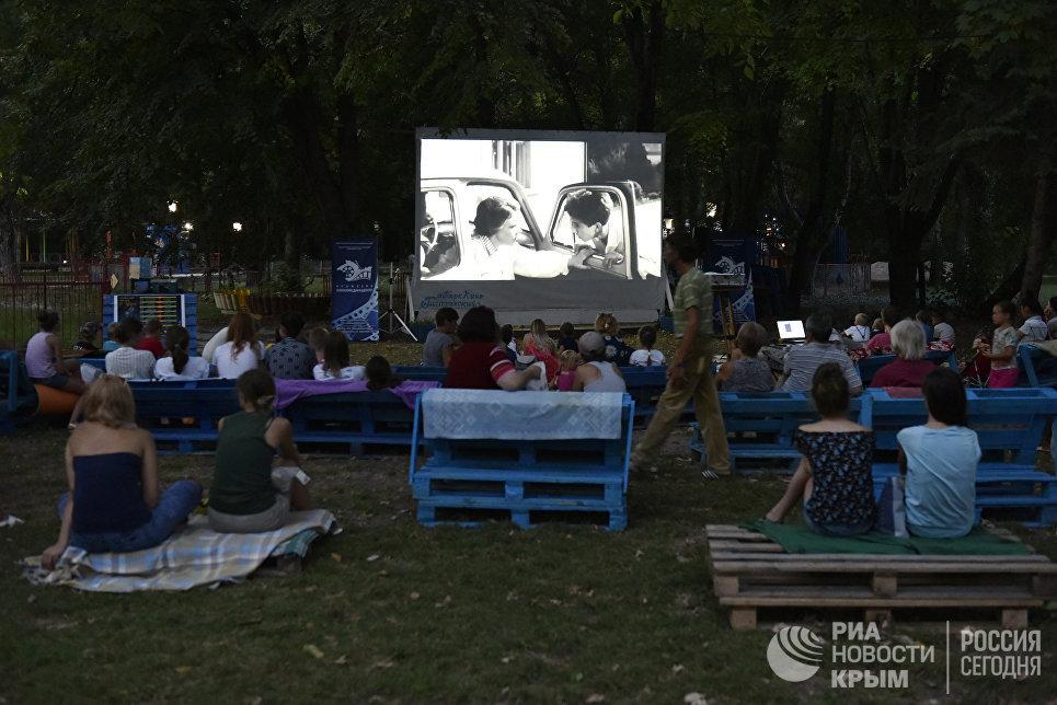 Люди смотрят фильм в летнем кинотеатре, который находится в парке им. Гагарина в Симферополе
