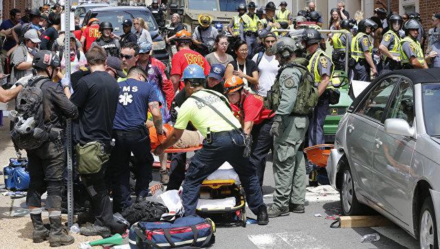 Спасатели помогают пострадавшим после того, как автомобиль врезался в толпу противников акции ультраправых, которая проходит в городе Шарлоттсвилл в штате Вирджиния