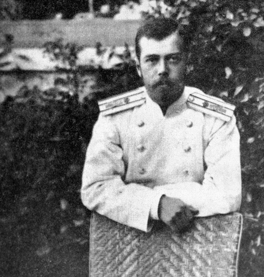 Император Николай II стоит оперевшись на соломенное кресло