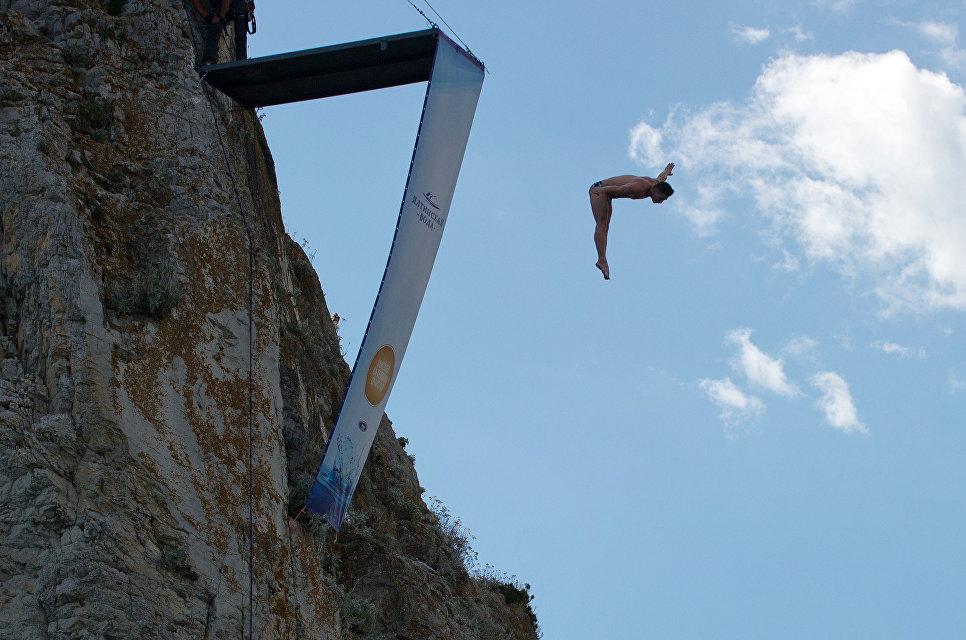 Спортсмен выполняет прыжок на тренировочной базе для занятия хай-дайвингом на скале Дива в Симеизе в Крыму.