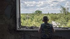Подросток у окна в разрушенном спортивном зале средней школы в Горловке. Архивное фото