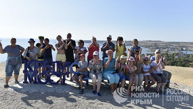 Люди на скамейке Крымский мост в Керчи наблюдают за морской операцией установки железнодорожной арки моста через Керченский пролив
