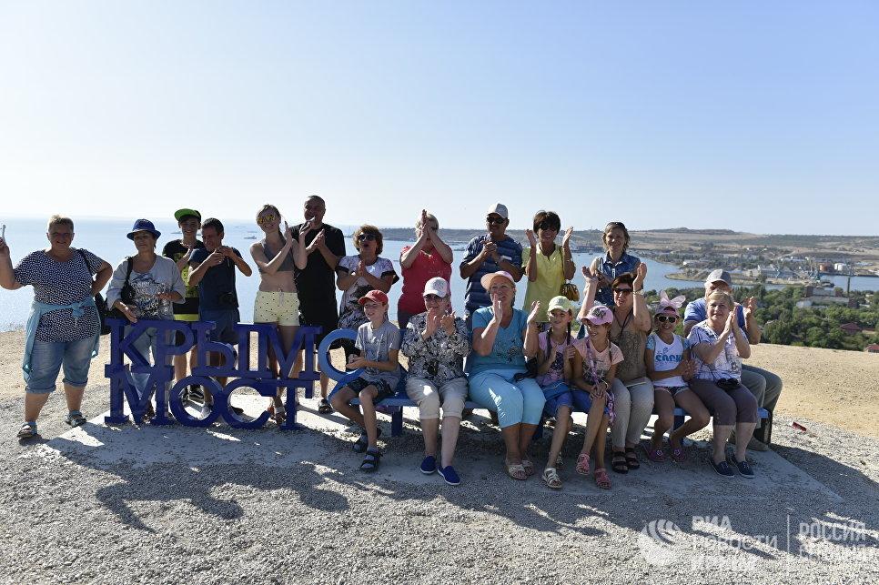 """Люди на скамейке """"Крымский мост"""" в Керчи наблюдают за морской операцией установки железнодорожной арки моста через Керченский пролив"""