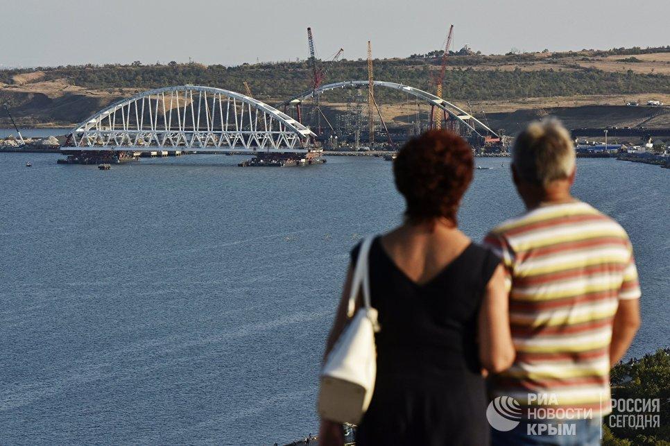 Люди смотрят на морскую операцию по транспортировке железнодорожной арки Крымского моста