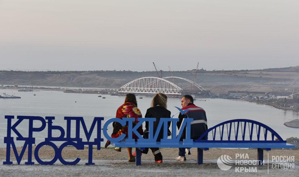 Люди на скамейке Крымский мост наблюдают за морской операцией установки железнодорожной арки моста через Керченский пролив