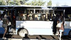 Люди заходят в переполненный автобус на остановке в Симферополе