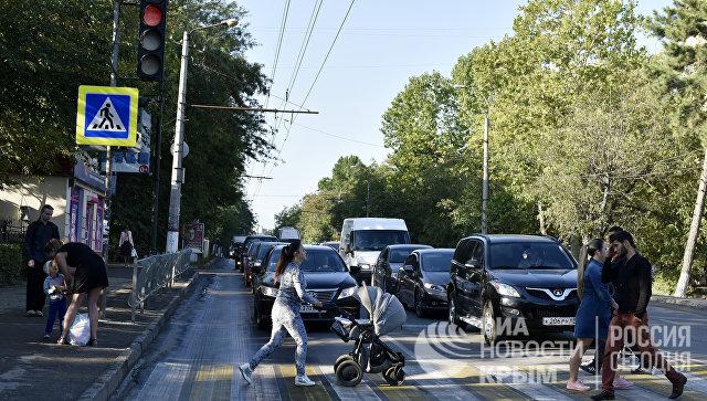 Люди переходят по пешеходному переходу дорогу в Симферополе