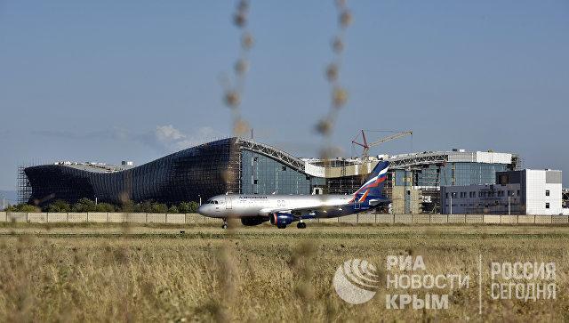 Самолет на фоне строящегося нового терминала аэропорта Симферополь