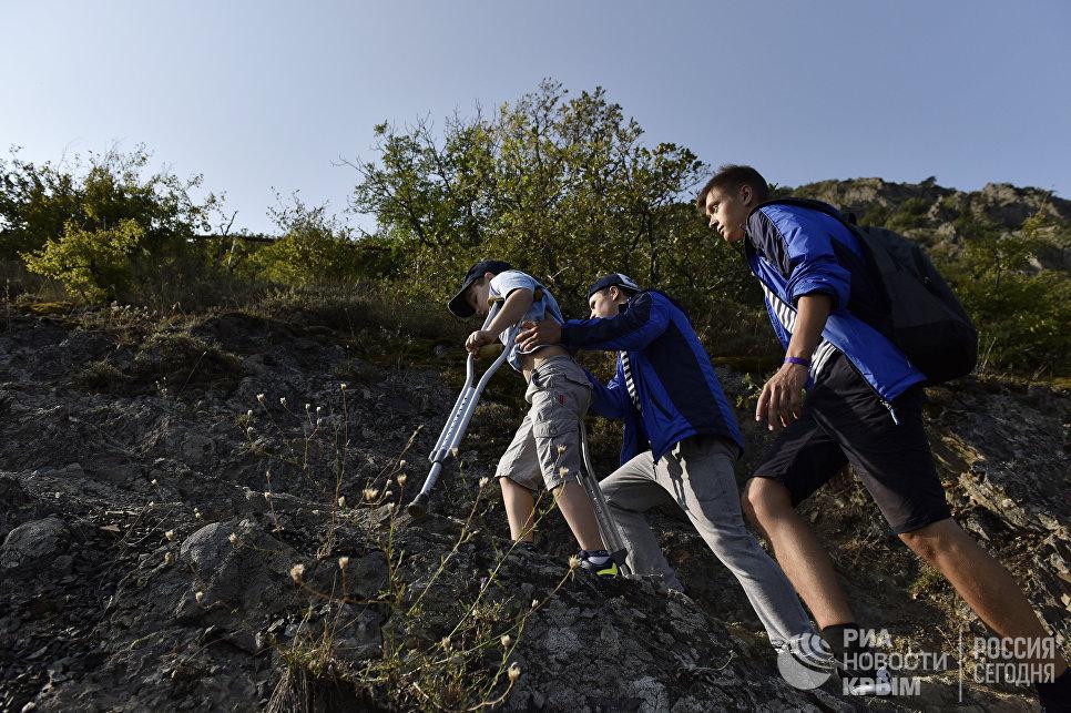 Здоровые дети помогают детям с ограниченными физическими возможностями в МДЦ Артек поднимаются на Аю-Даг для посвящения в артековцы
