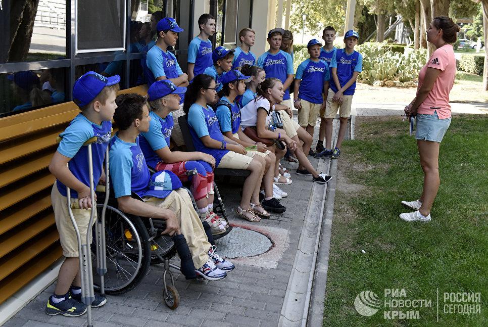 """Дети с ограниченными физическими возможностями на смене в МДЦ """"Артек"""" общаются с вожатой отряда"""