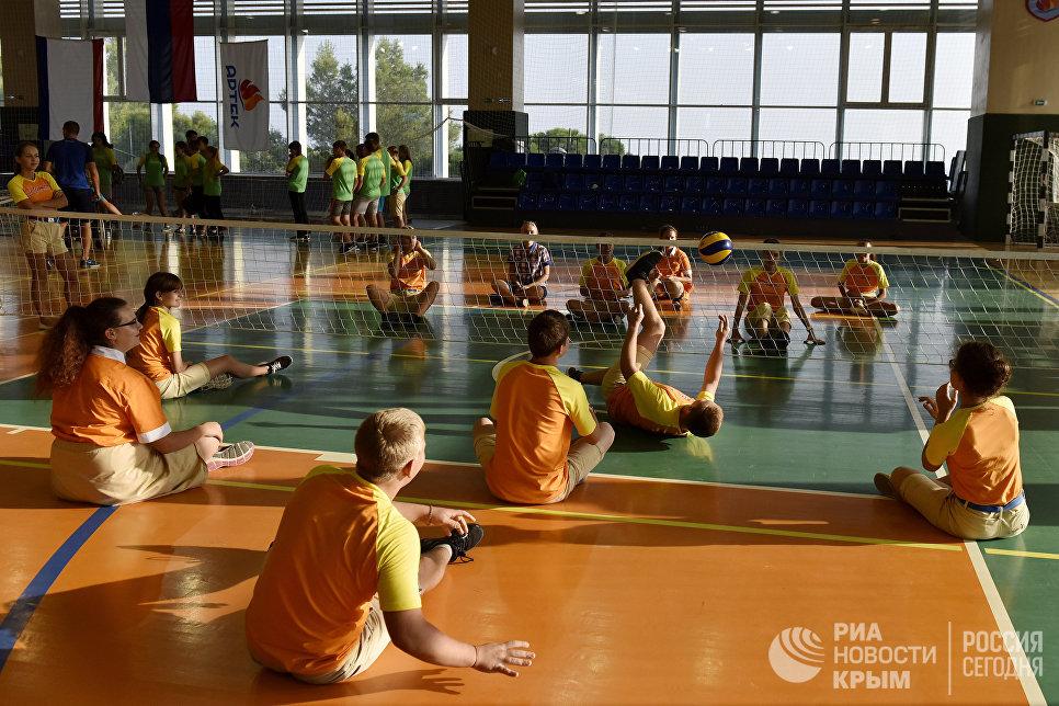 Здоровые дети играют в волейбол сидя на полу в день равных возможностей в МДЦ Артек
