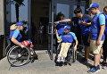 Дети с ограниченными физическими возможностями помогают друг другу перед входом в столовую в МДЦ Артек