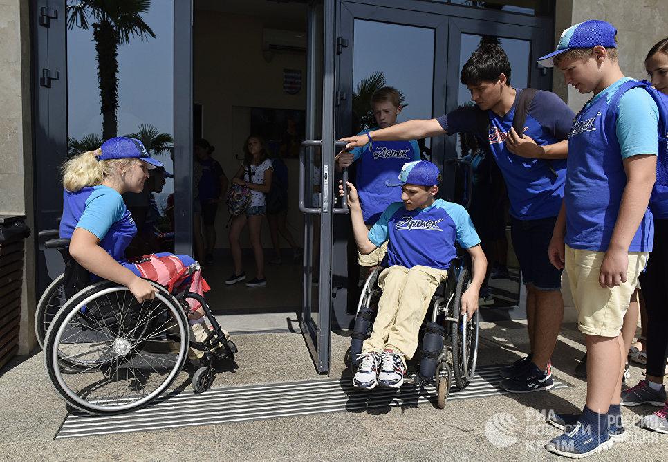"""Дети с ограниченными физическими возможностями помогают друг другу перед входом в столовую в МДЦ """"Артек"""""""