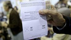 Мужчина держит бюллетень на избирательном участке в Барселоне, Испания. 1 октября 2017