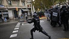 Испанская полиция стреляет резиновыми пулями по людям, пытающимся добраться до места голосования в Барселоне, Испания. 1 октября 2017