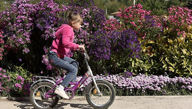 Девочка катается на велосипеде в Ботаническом саду Крымского федерального университета им.Вернадского в Симферополе