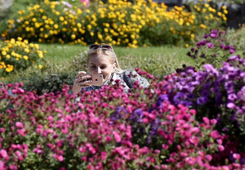 Женщина фотографирует цветы в Ботаническом саду Крымского федерального университета им.Вернадского в Симферополе