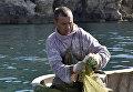 Рыбак достает рыбу из сетей во время ловли рыбы на мысе Тарханкут. Большой Атлеш