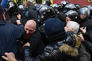 Участники вече у здания Верховной рады в Киеве и сотрудники правоохранительных органов во время драки у автомобиля с аппаратурой.
