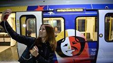 Девушка на фоне тематического поезда Сердце России на станции Бейкер-Стрит лондонского метро